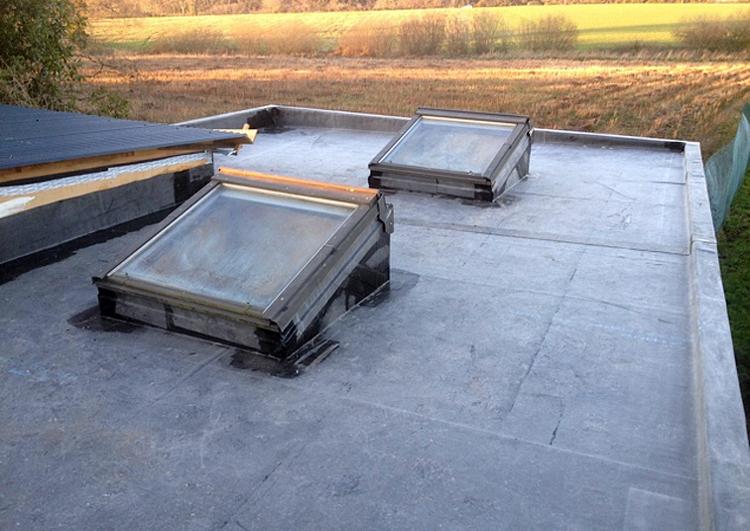 toiture plate couverte en membrane EPDM bordée par des acrotères, avec deux vélux, au fond un champ moissonné.