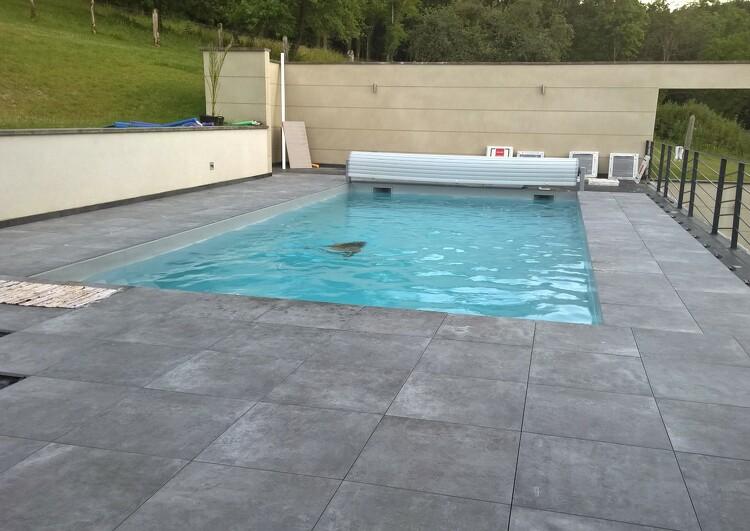 toiture terrasse avec une piscine, dalles sur plots, à gauche quelques dalles manquantes laisse voir la membrane EPDM, au fond un mur, à gauche des garde-corps, à l'arrière plan de la végétation.