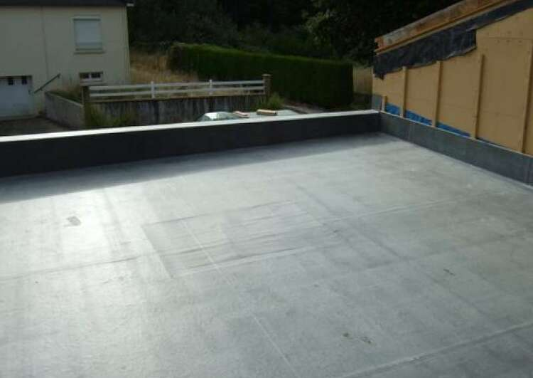 au premier plan la toiture plate est couverte en membrane EPDM, sur le coté droite il y a un mur de la construction voisine, au fond il y a une maison