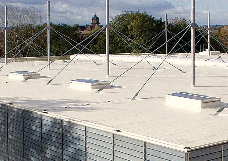 toiture plate couverte en membrane TPO blanche, à l'arrière plan le clocher d'une église dépasse de la végétation.