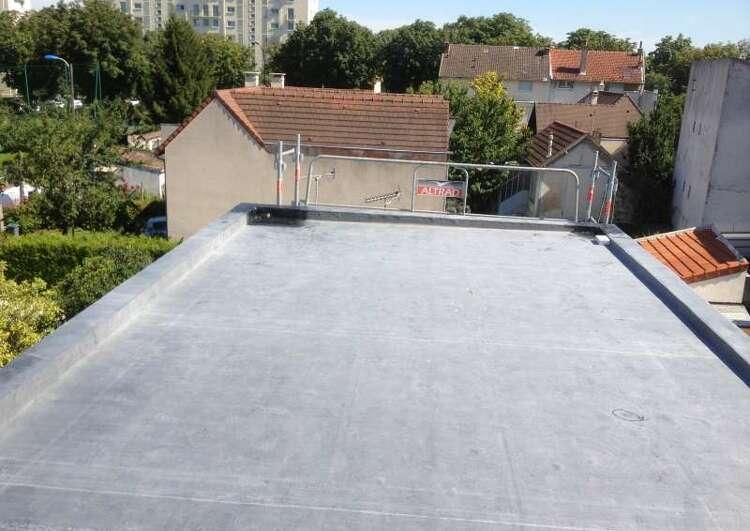 toiture plate bordée d'acrotères, couverte en membrane EPDM, vue prise en hauteur, à l'arrière-plan on voit d'autres maison, un immeuble, et de la végétation.
