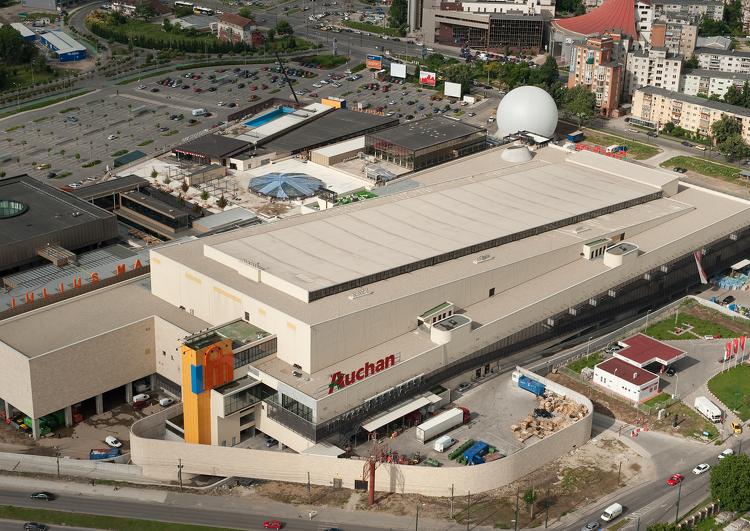 vue d'avion d'un supermarché Auchan couvert en membrane TPO, autour on peut voir le parking, des immeubles, la voirie.