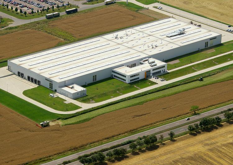 vue d'avion d'un grand bâtiment industriel entourée de champs, un parking et les routes d'accès.