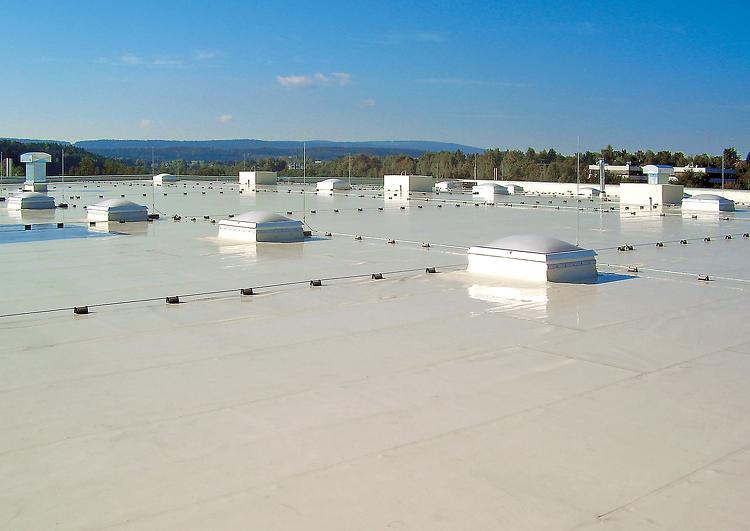 grande surface de toiture plate couverte en membrane TPO, avec de nombreux puits de lumière et sortie de ventilation, végétation et reliefs à l'arrière plan.