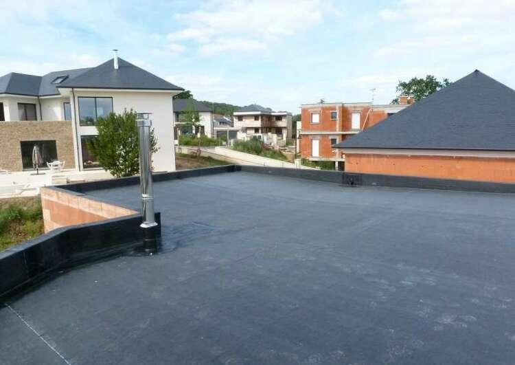 toit plat couvert en EPDM, la construction est en brique, à gauche une platine de poele, au fond les immeubles voisins