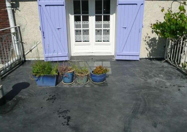 toit terrasse couvert en membrane EPDM, au fond un mur avec la porte fenêtre au volets bleus, de chaque coté des garde-corps, au milieu quatre plantes en pots.