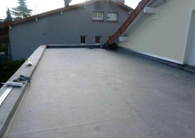 toiture plate couverte en membrane EPDM délimité à gauche et au fond par un acrotère, à droite par un mûr, des outils sont posés sur l'accrotère, à l'arrière-plan une maison.
