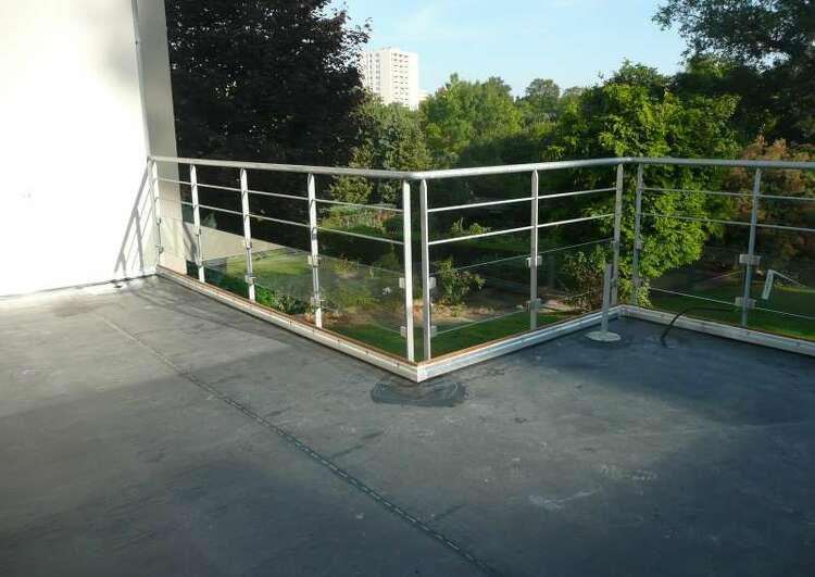 toit terrasse couvert en membrane EPDM bordé de barrières, à l'arrière-plan un jardin.