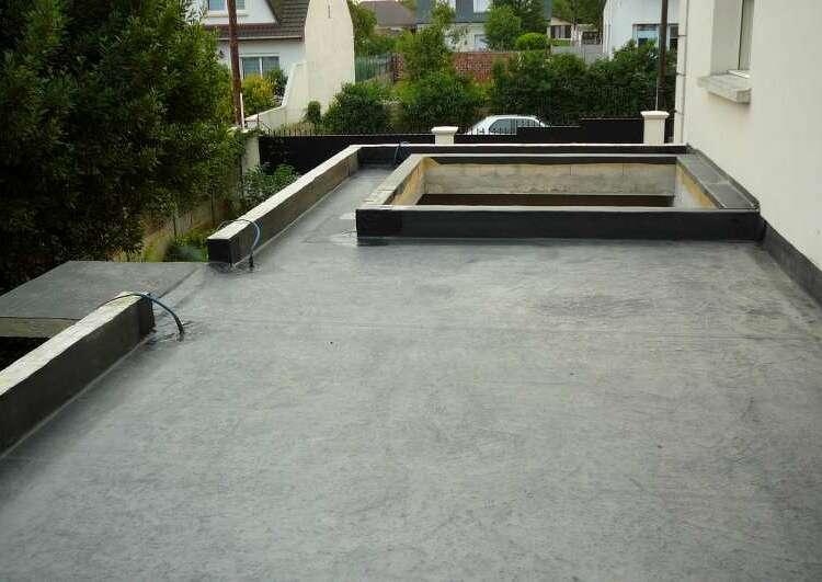 toiture plate couverte en membrane EPDM, bordée par des acrotères sauf à droite par un mur, une zone non couverte au milieu de la toiture est bordée d'accrotères aussi, l'arrière plan montre une zone résidentielle.