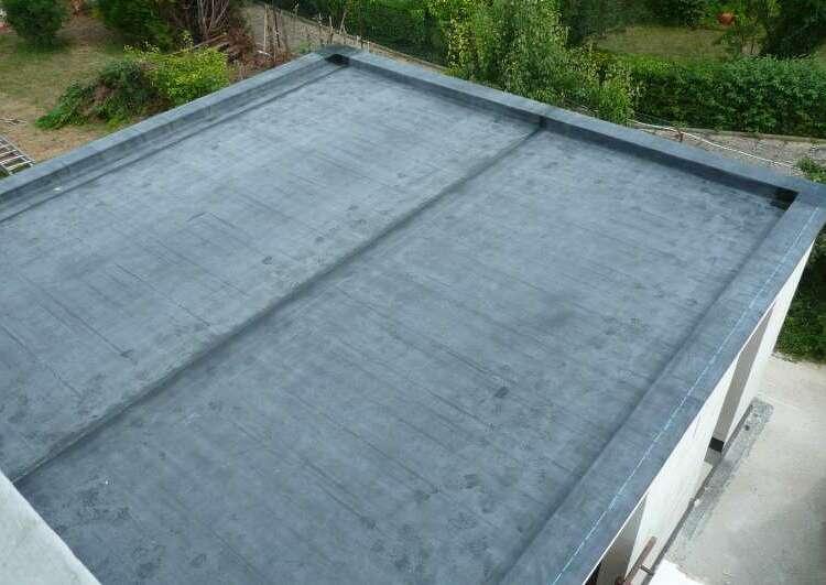 toiture plate couverte en membrane EPDM vue prise en hauteur, autour du toit on distingue un jardin et un terrasse.