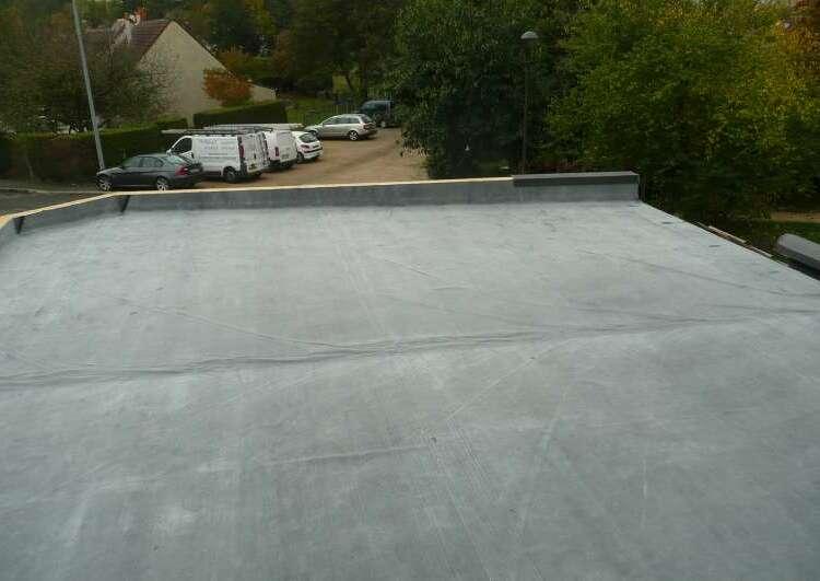 toiture plate couverte en membrane EPDM, l'arrière plan montre une zone résidentielle.