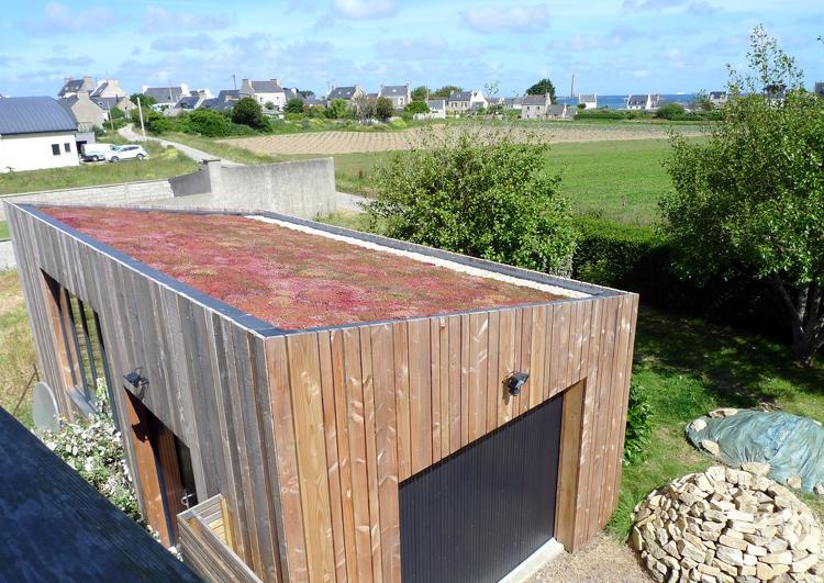 garage avec bardage en bois et toiture en pente douce avec une végétalisation extensive, à l'arrière plan un champ et un village.