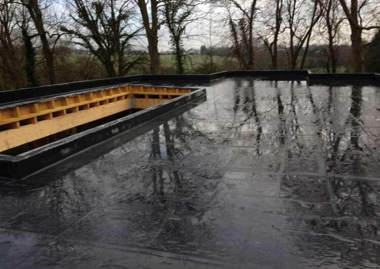 toiture en membrane EPDM collé sur panneaux OSB sur un chantier ossature bois sous la pluie