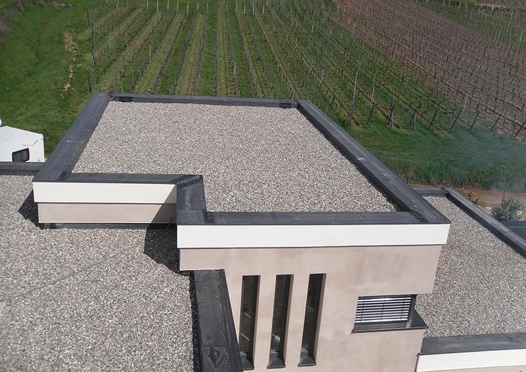 au premier plan toiture plate sur trois niveaux étanchéité EPDM lesté par des galets. Champ de vigne à l'arrière plan.