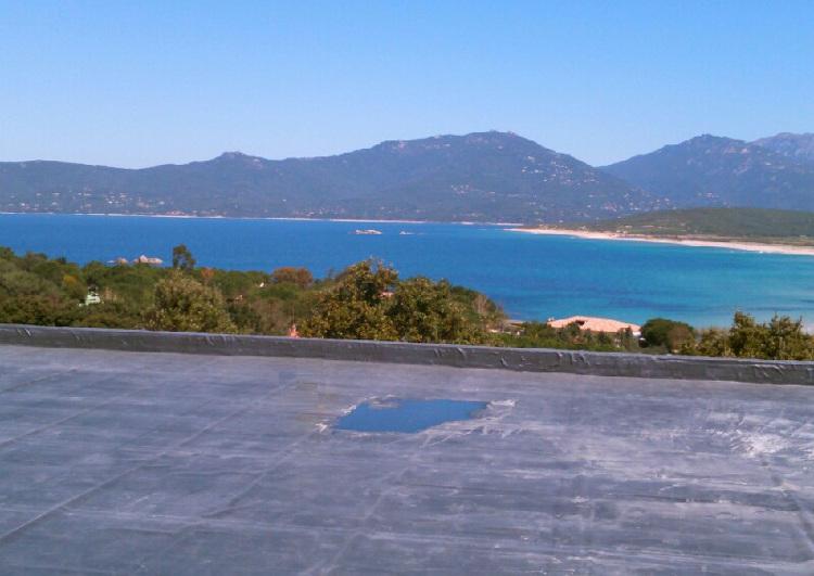 au premier plan une toiture plate avec acrotère, couverture en membrane EPDM, à l'arrière plan vue sur la mer, la cote avec une plage à droite et des montagnes au fond.