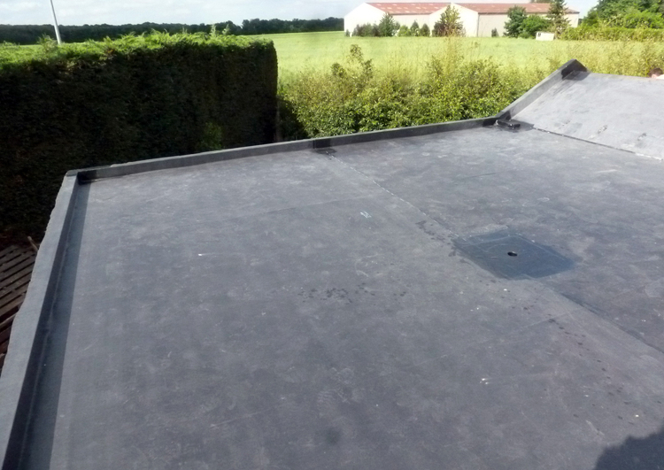 toiture plate couverte en membrane EPDM, un évacuation d'eau pluviale au milieu du toit, à l'arrière-plan un champ et des bâtiments agricoles.