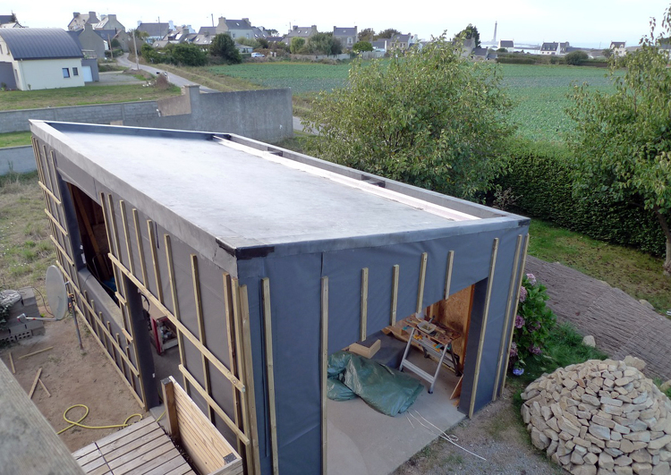 chantier d'un garage en ossature bois avec toiture en pente douce couverte en membrane EPDM avant la pose du système de végétalisation.