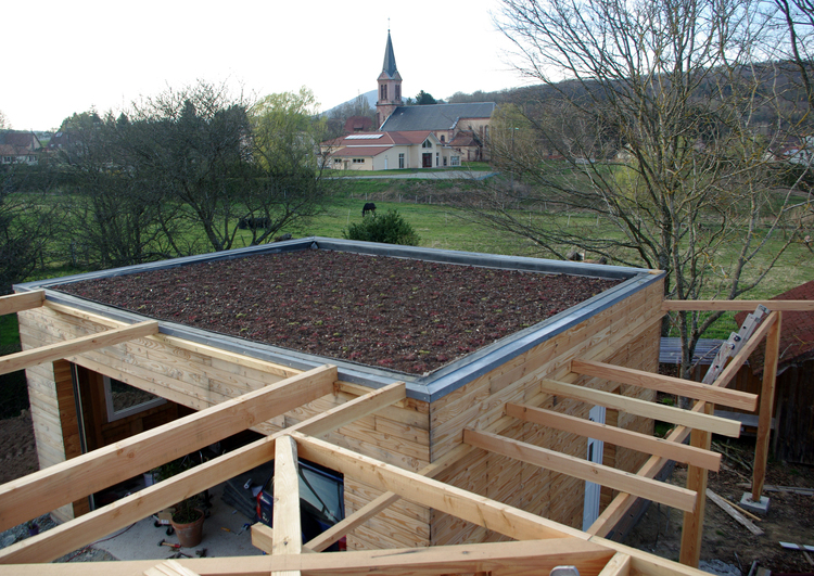 chantier d'un garage en ossature bois avec une toiture plate végétalisée, le substrat est très visible. à l'arrière plan un champ et un village avec une église.