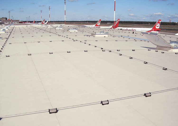grande surface de toiture plate couverte en membrane TPO, à l'arrière plan des avions de grandes lignes et les pistes de l'aéroport.