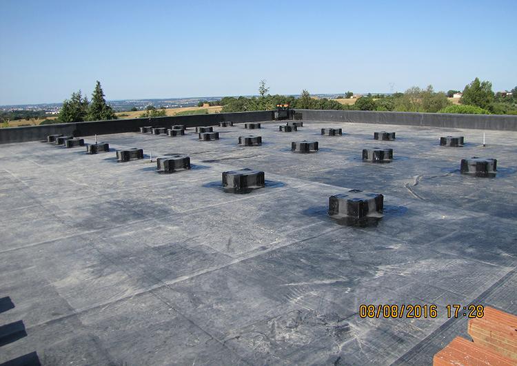 Au premier plan vaste toiture plate avec étanchéité en EPDM, à l'arrière plan paysage de plaine de Haute Garonne