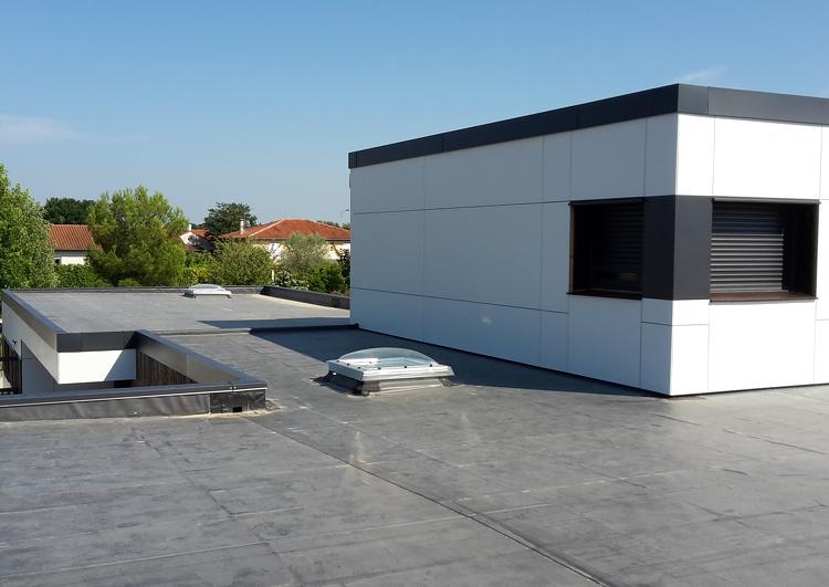 toiture plate au formes complexes couvertes en membrane EPDM, acrotères, puits de lumière, mur avec une fenêtre sur la gauche, à l'arrière plan une zone résidentielles avec des grands arbres.